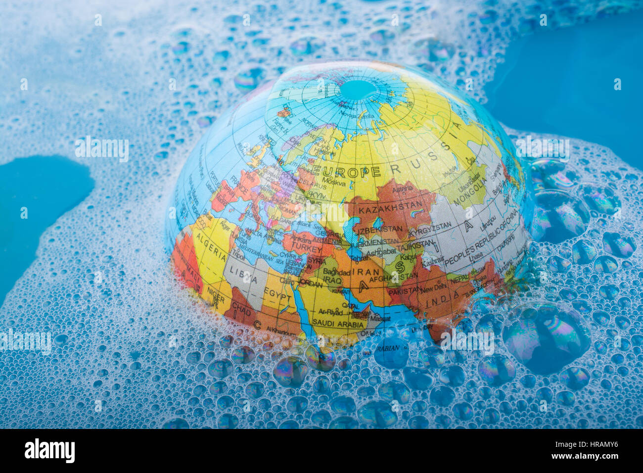 362ef2ce580b Paint brush placed on the top of globe in a water covered with foam ...