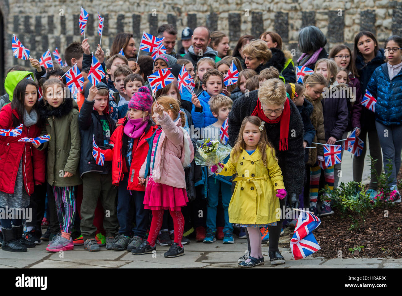 London, UK. 28th Feb, 2017. Molly (yellow coat, aged three) waits to give the Queen some flowers - The Queen, accompanied - Stock Image