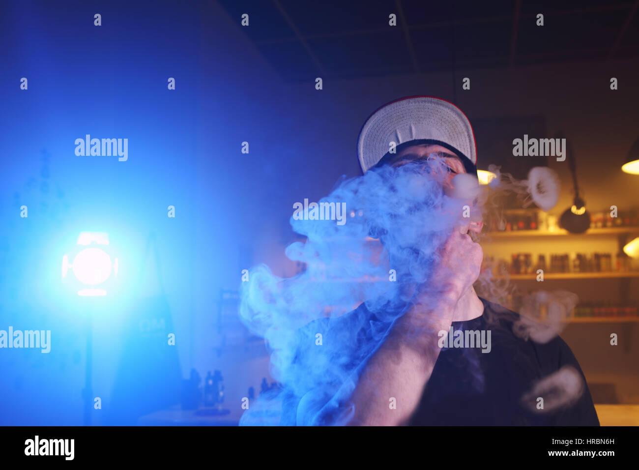 Vape. Vaping man in a cloud of vapor. Photo is taken in a vape bar. - Stock Image