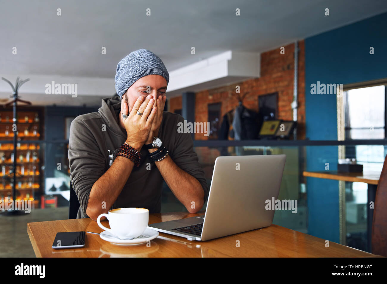 Worried shoked man looking on laptop at cafe - Stock Image