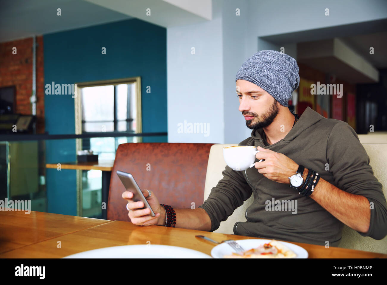 Young handsome hipster man with beard sitting in cafe talking mobile phone, holding cup of coffee. - Stock Image