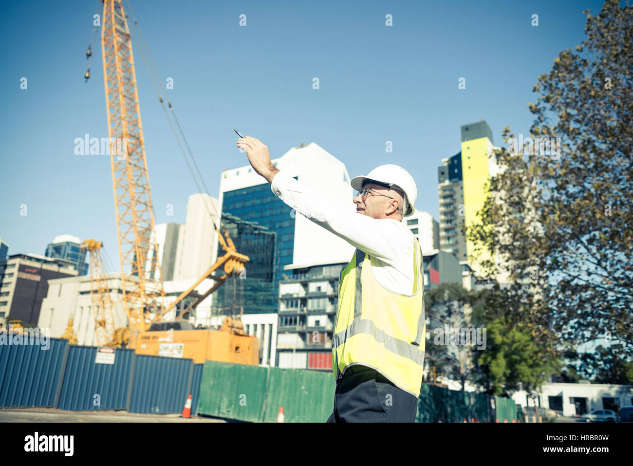 Senior foreman in glasses doing his job at building area on sunn - Stock Image
