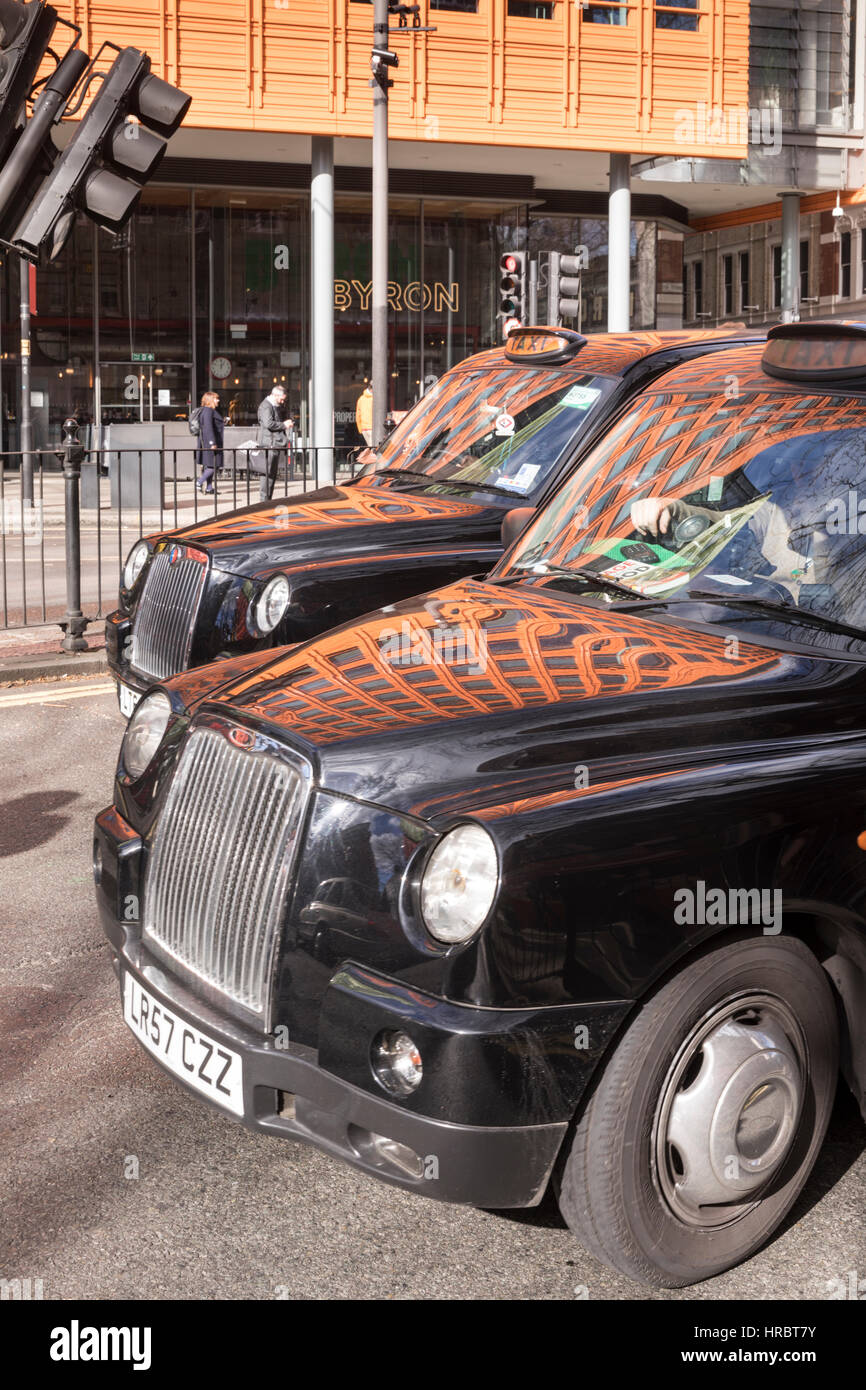 Reflection of Renzo Piano designed Central St Giles development on bonnets of London Taxis, St Giles High St, London, - Stock Image