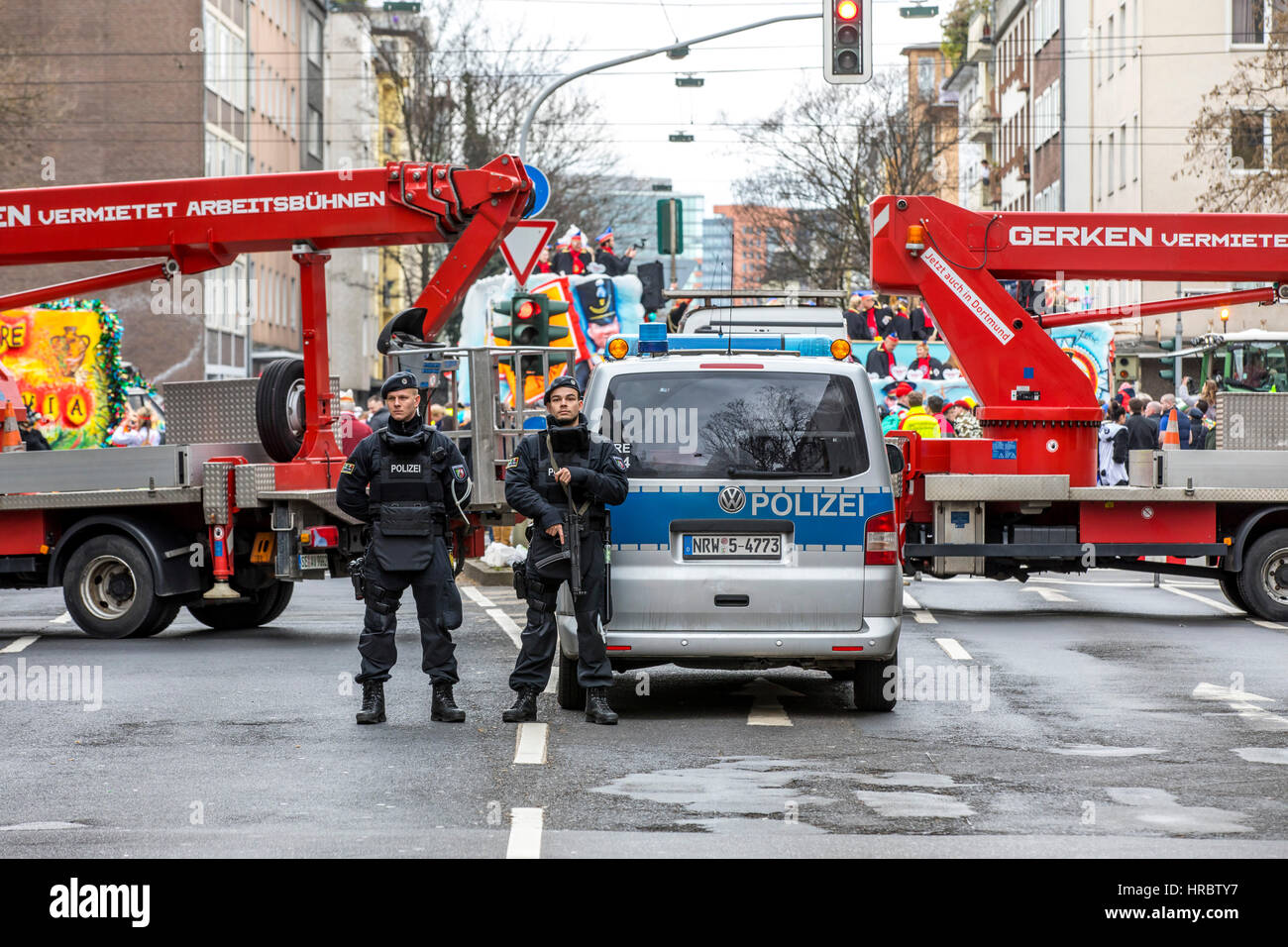 German Carnival parade in Düsseldorf, Police officers secure the parade, blocking roads with trucks, against terrorist Stock Photo
