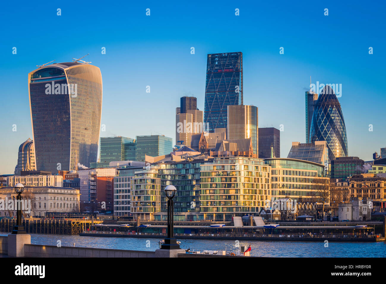 London, UK - The world famous business district of London with skyscrapers and clear blue sky at sunrise - Stock Image