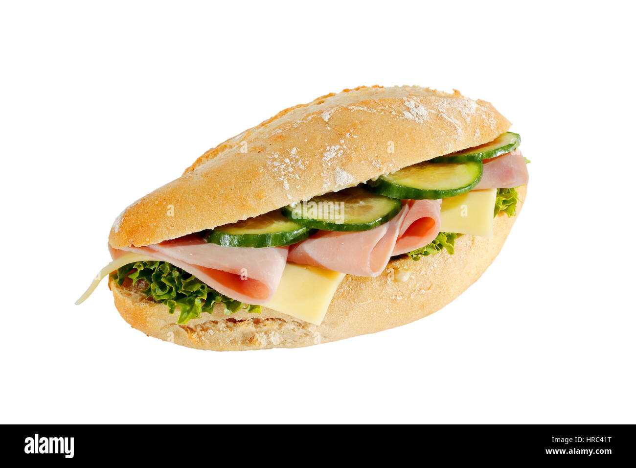 Baguette roll with ham, cheese, lettuce and cucumber slices, isolated - Stock Image