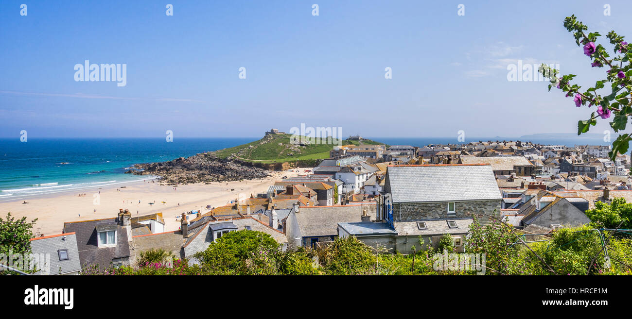 United Kingdom, Cornwall, St Ives, view over the roofs of St Ives with Porthmeor Beach and the Island Peninsula Stock Photo