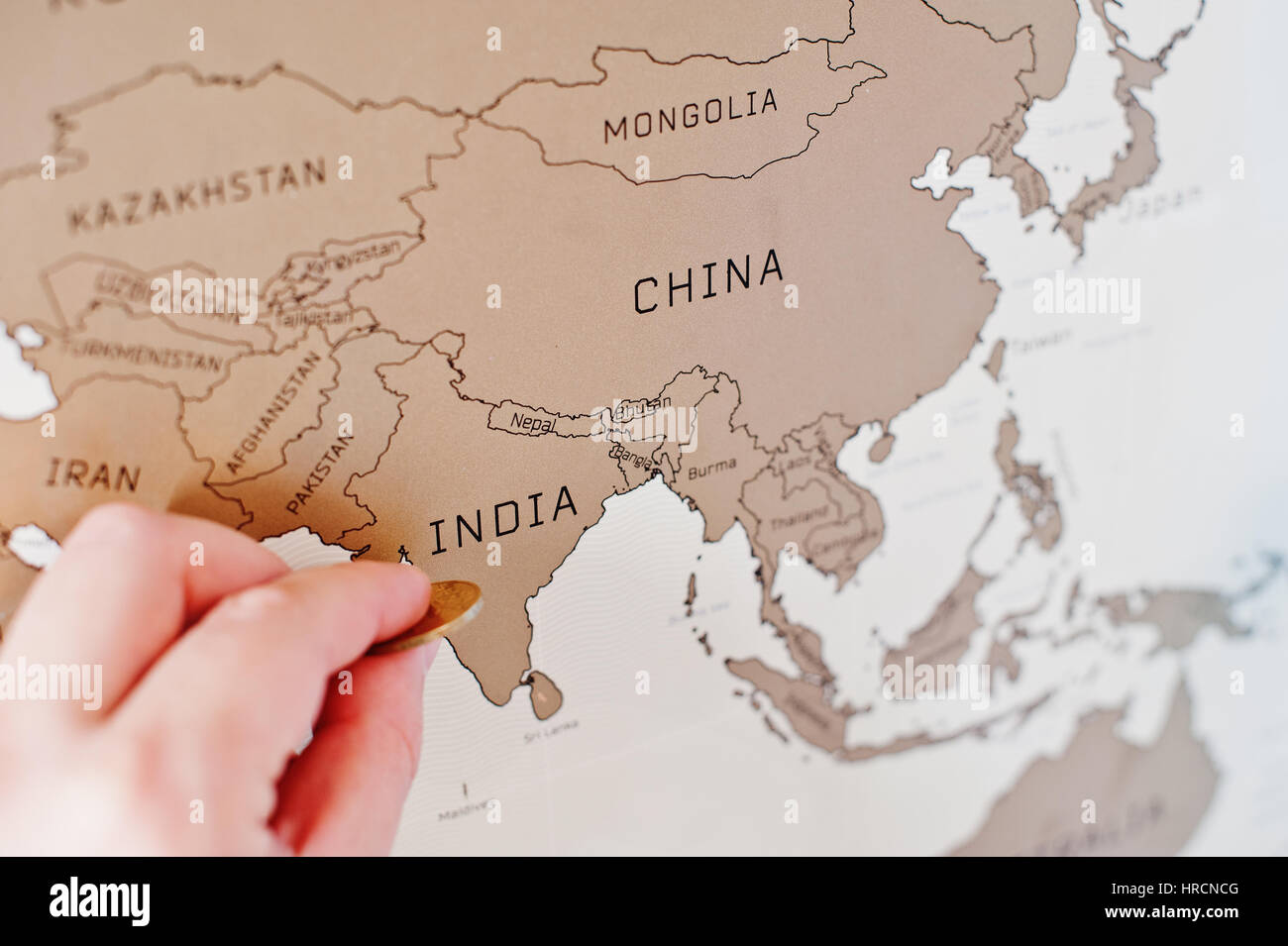 Scratch travel map of the world. Hand of man erase India ... on