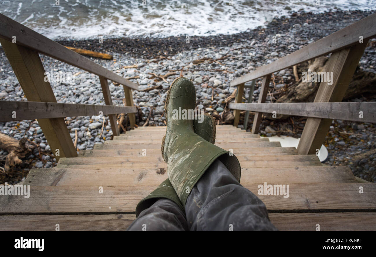 Man legs in dirty rubber boots after a day walking on the beach - Stock Image