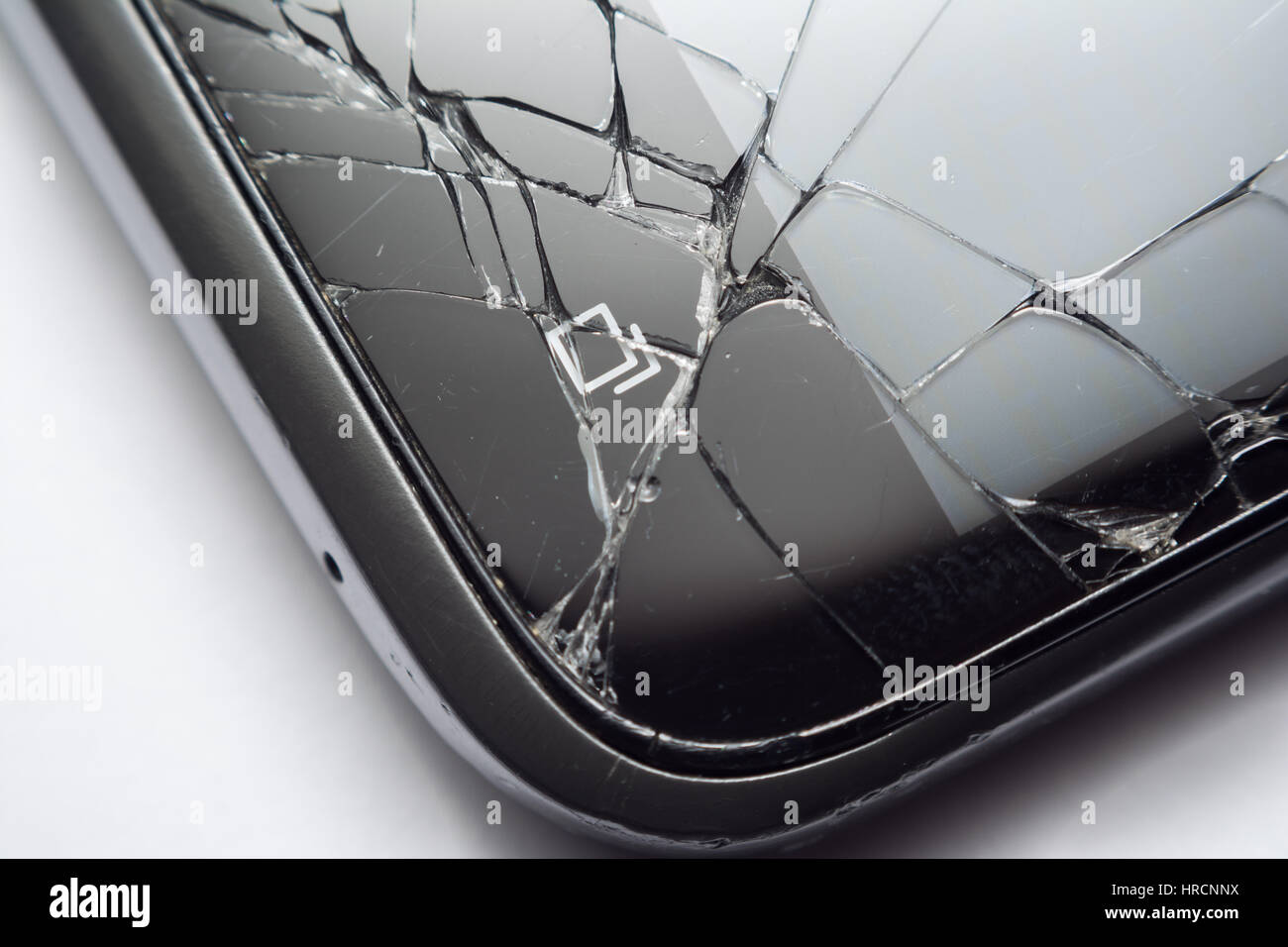 Close up of a cracked smartphone screen after being dropped on the ground. Concept for broken phones. - Stock Image