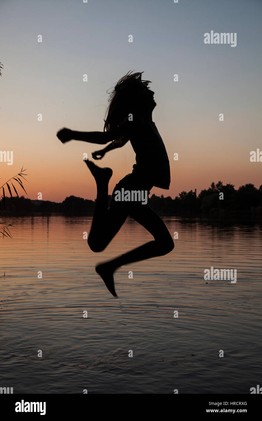 Portrait Of Girl Jumping Into The Water Silhouette Stock Photo