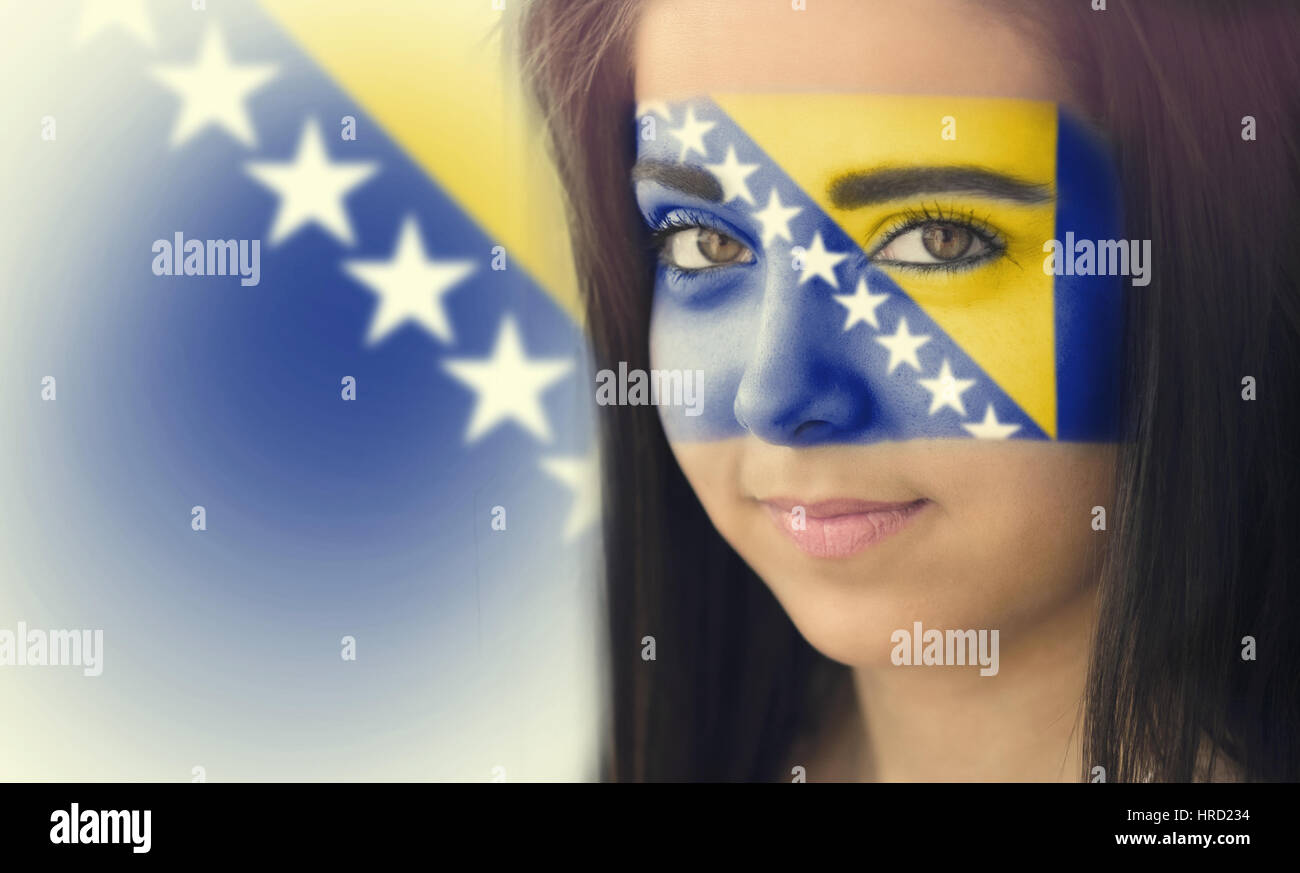 The flag of Bosnia and Herzegovina on the face of a smiling woman. / Color effects and custom white balance is added - Stock Image