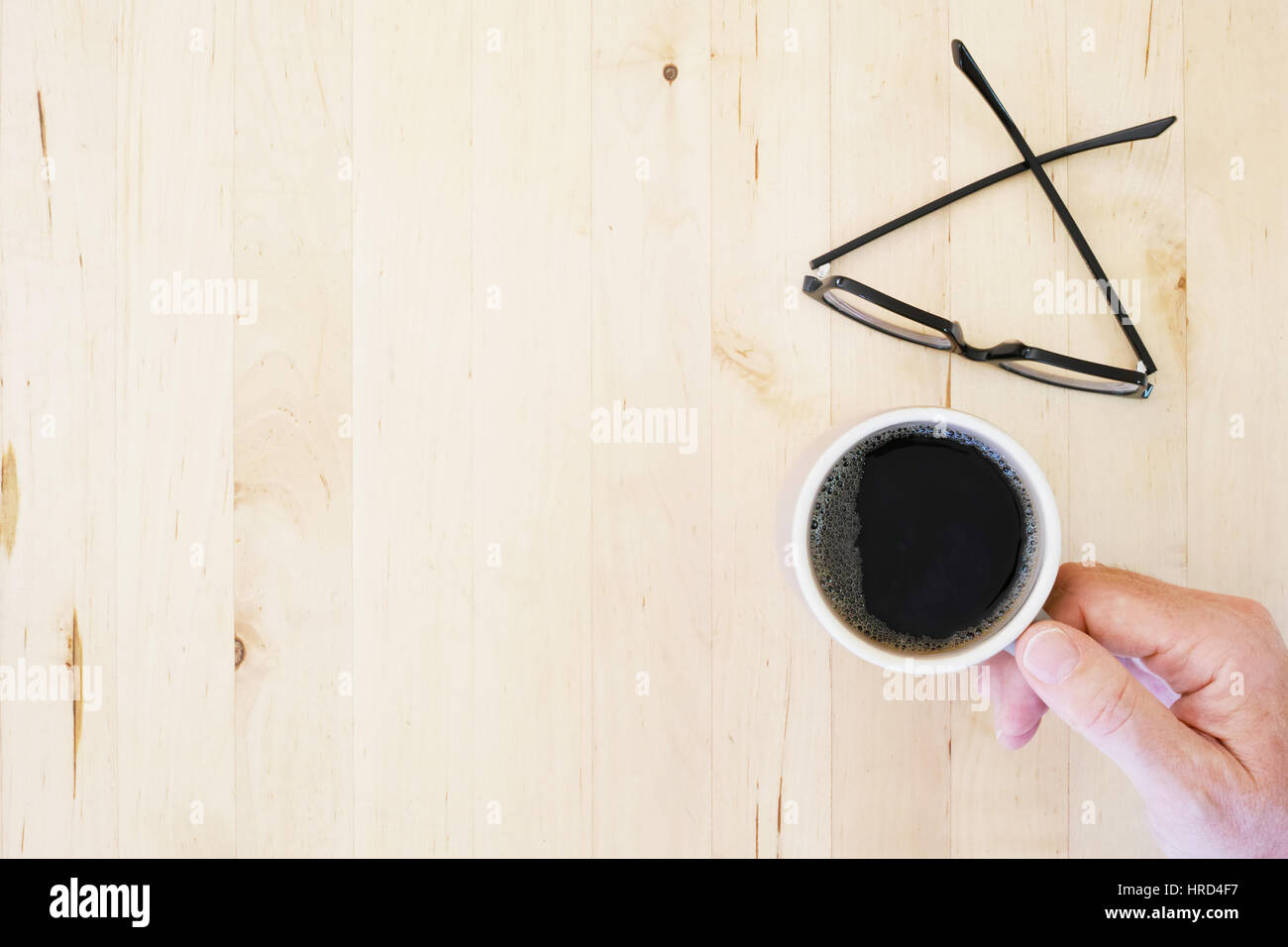 Hand reaching for coffee mug, eyeglasses on wooden tabletop. Top view. - Stock Image