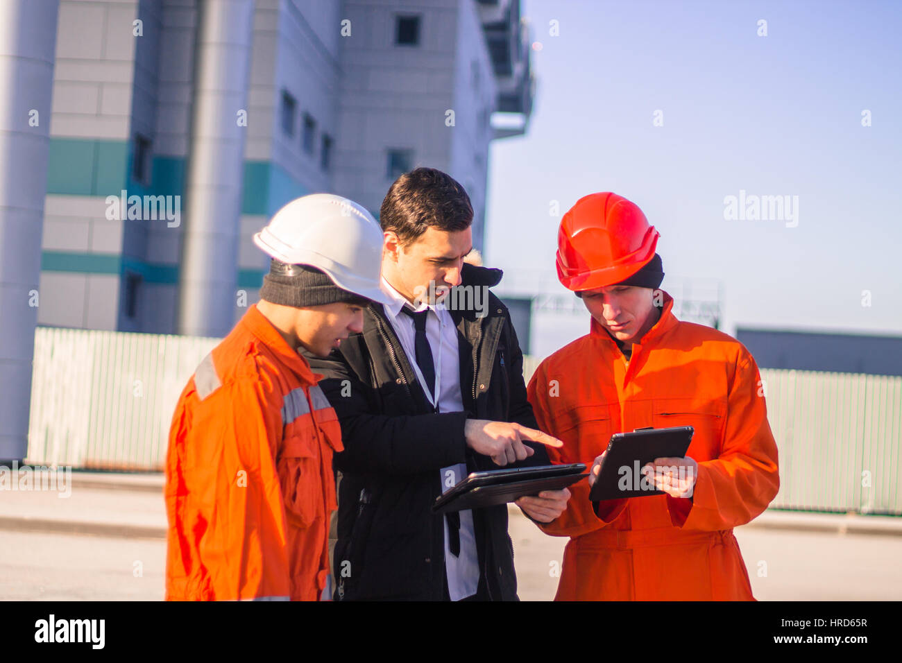 boss or Chief  instructs young team of  young engineers with a construction project on tablet. Technology in work. - Stock Image