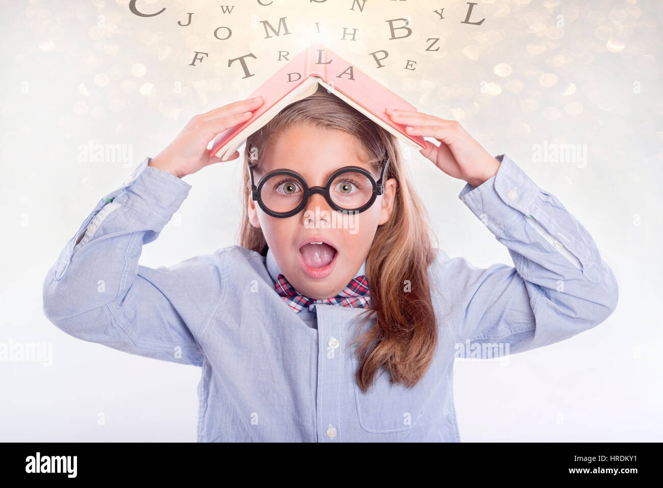 Surprised girl with book on her head, back to school - Stock Image
