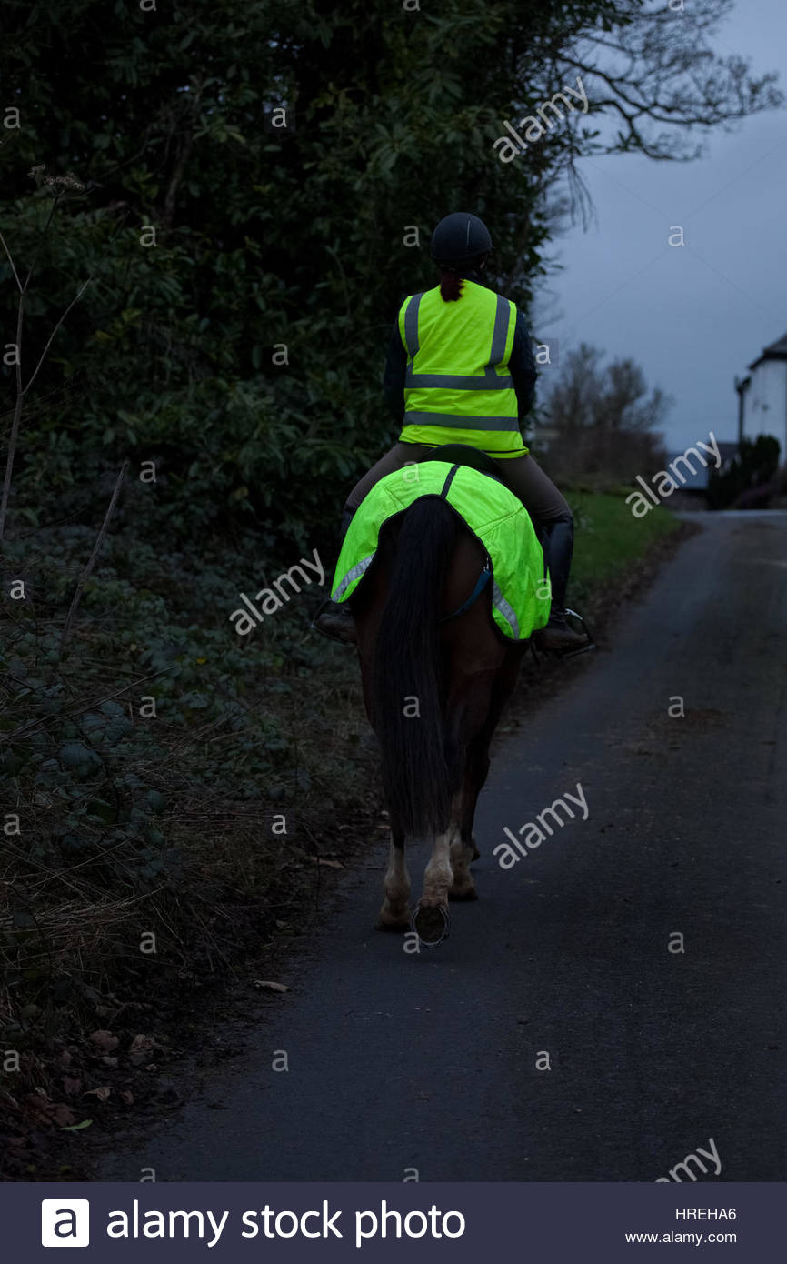 Horse rider riding dark country lane wearing reflective clothing UK. - Stock Image