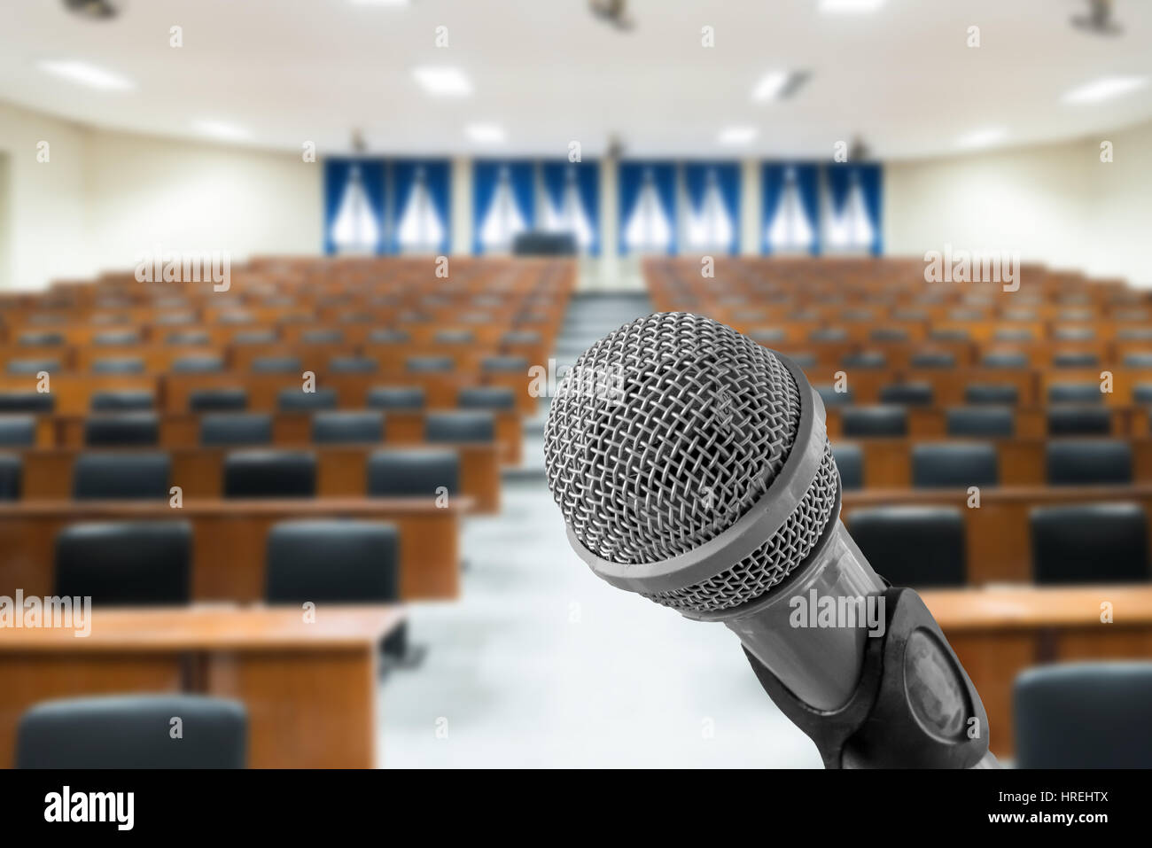 Microphone with blurred photo of empty conference hall or seminar room in background. Business meeting concept - Stock Image