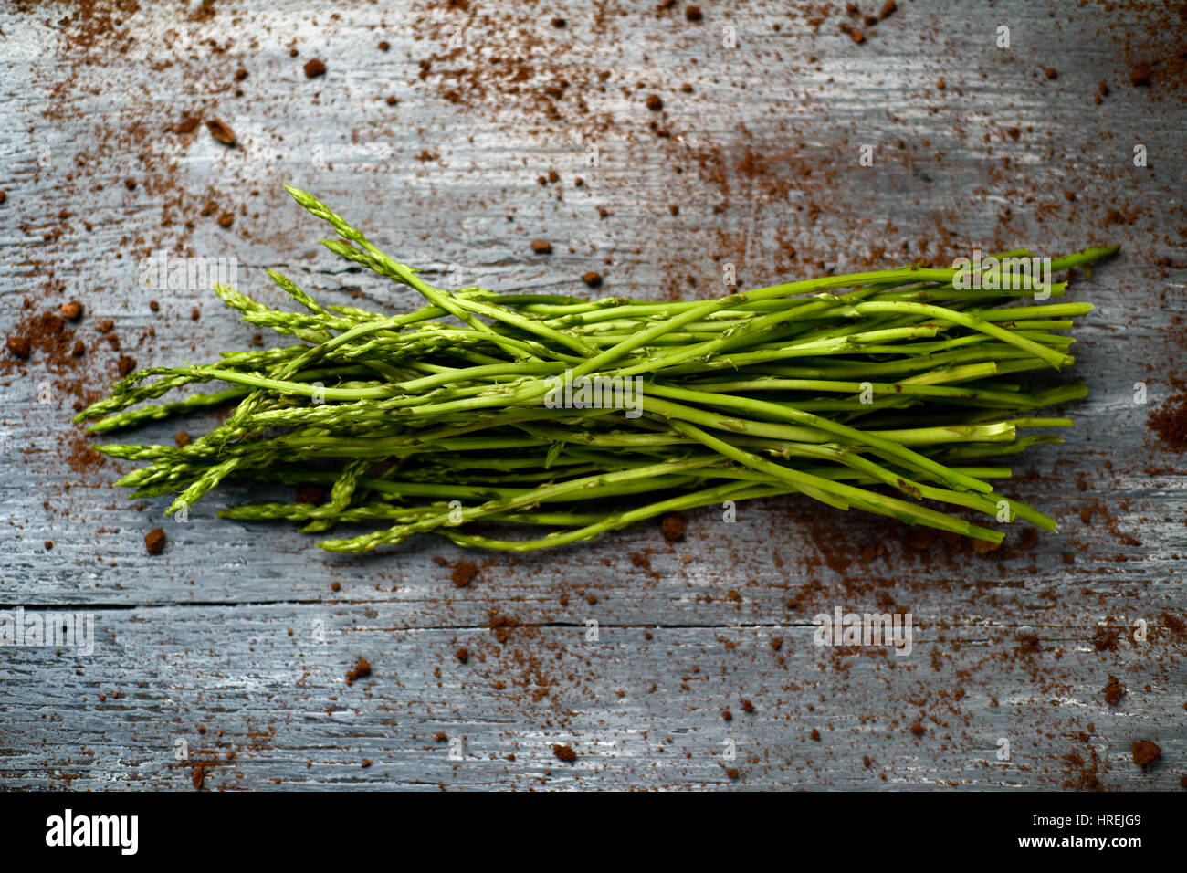 high-angle shot of a bunch of wild asparagus on a rustic wooden surface Stock Photo