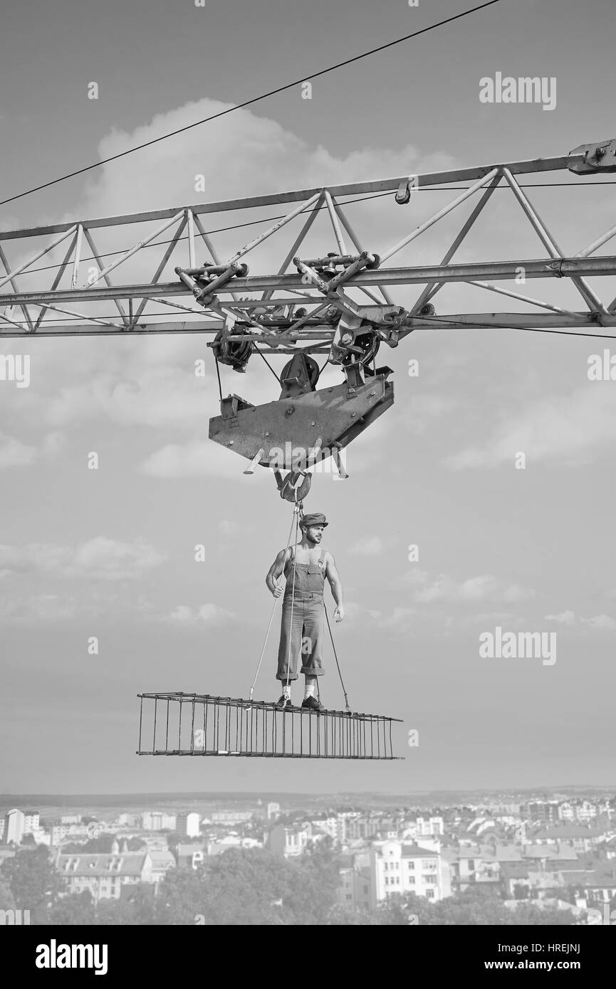 Developing city. Vertical monochrome shot of a retro builder at construction site professionalism vintage work worker - Stock Image