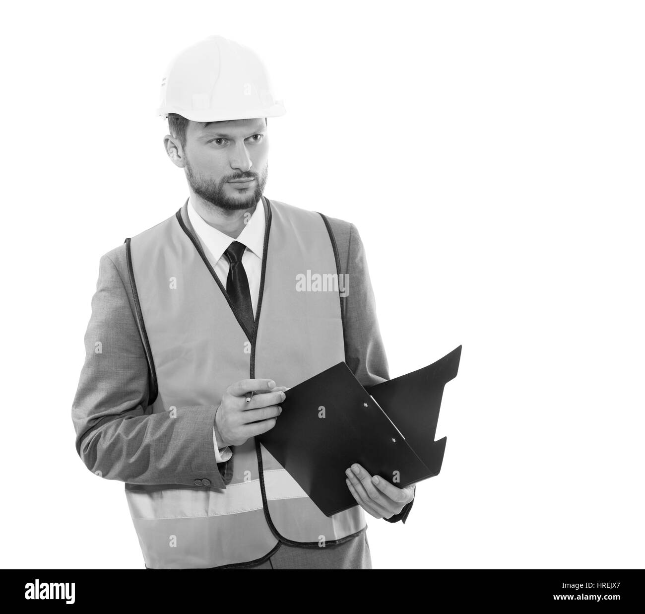 Businessperson on work. Monochrome shot of a businessman constructionist wearing protective helmet and safety vest - Stock Image