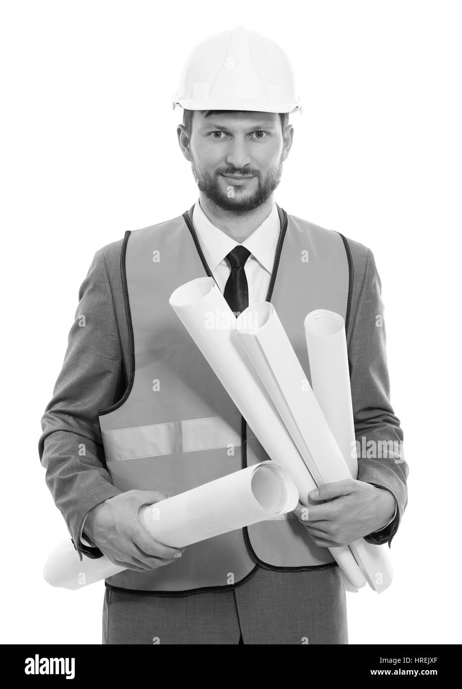 Business developer. Vertical monochrome shot of a businessman architect in a safety vest and hardhat smiling to - Stock Image