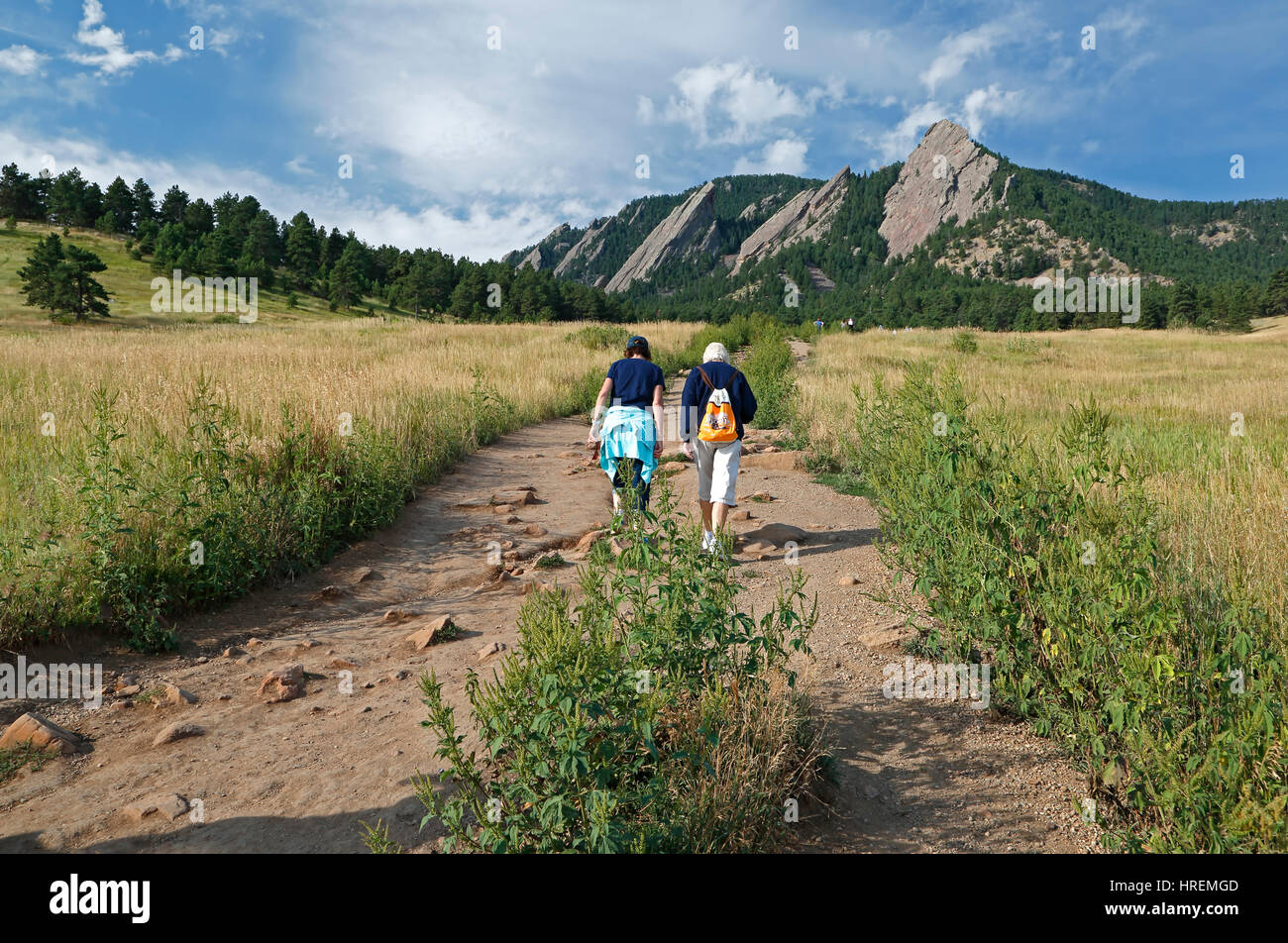 Hikers on trail and Flatirons, from near Chautauqua Meadow Trailhead, Boulder, Colorado USA - Stock Image