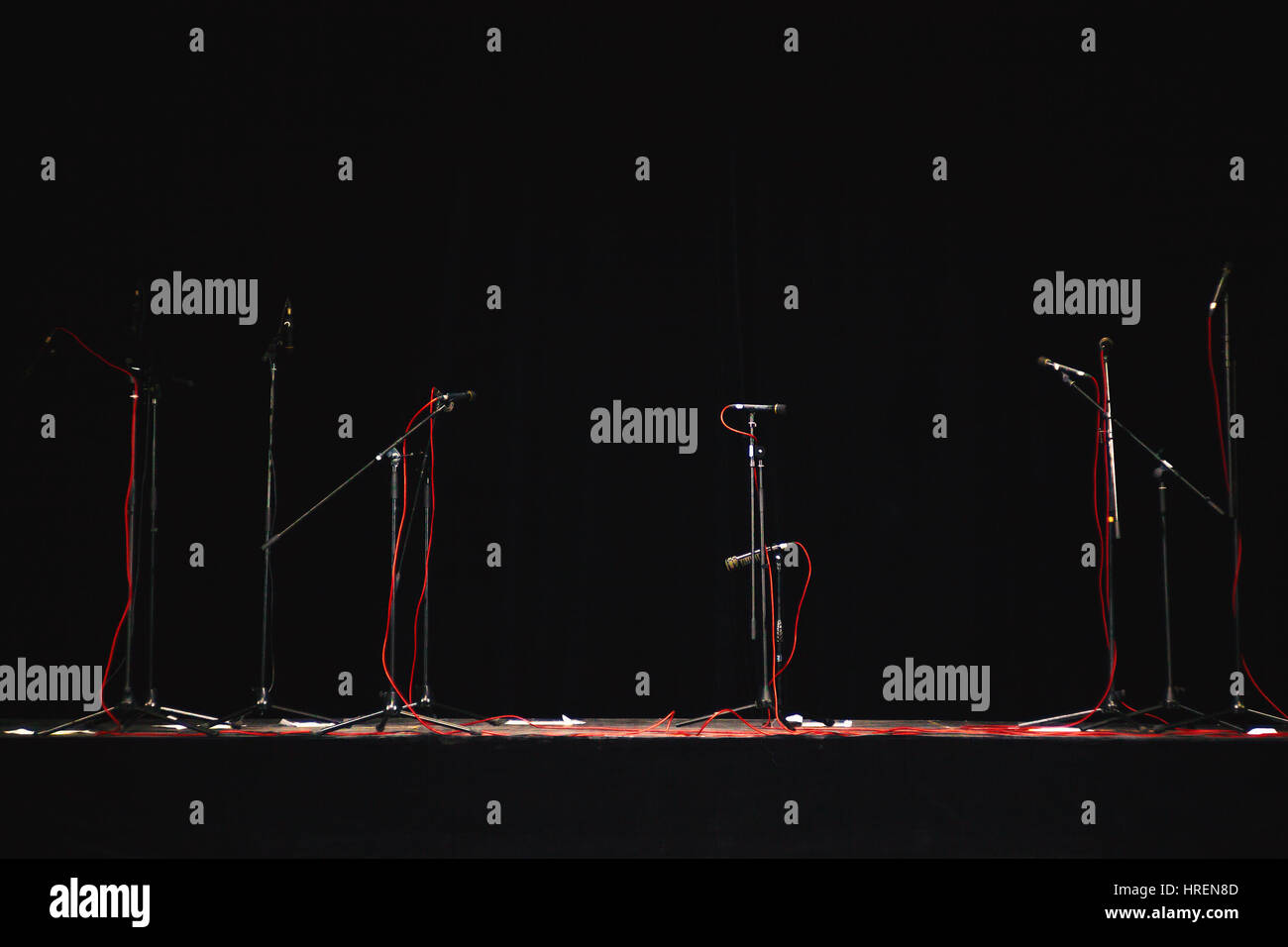 Concert stage details, just a few microphones on stands and red cords ready for live performance. - Stock Image