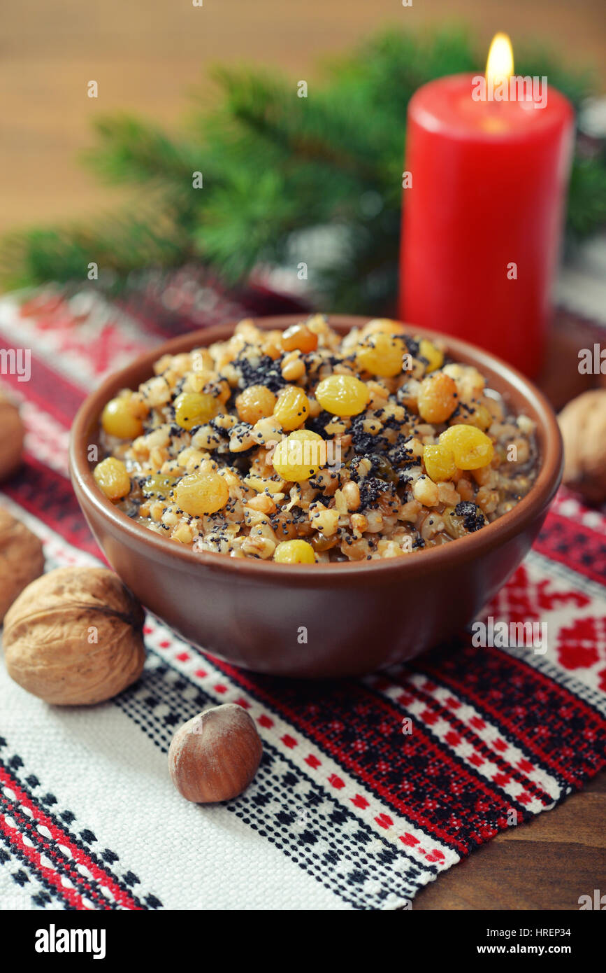 Traditional Christmas slavic dish kutia in ceramic bowl with spoon and candle - Stock Image