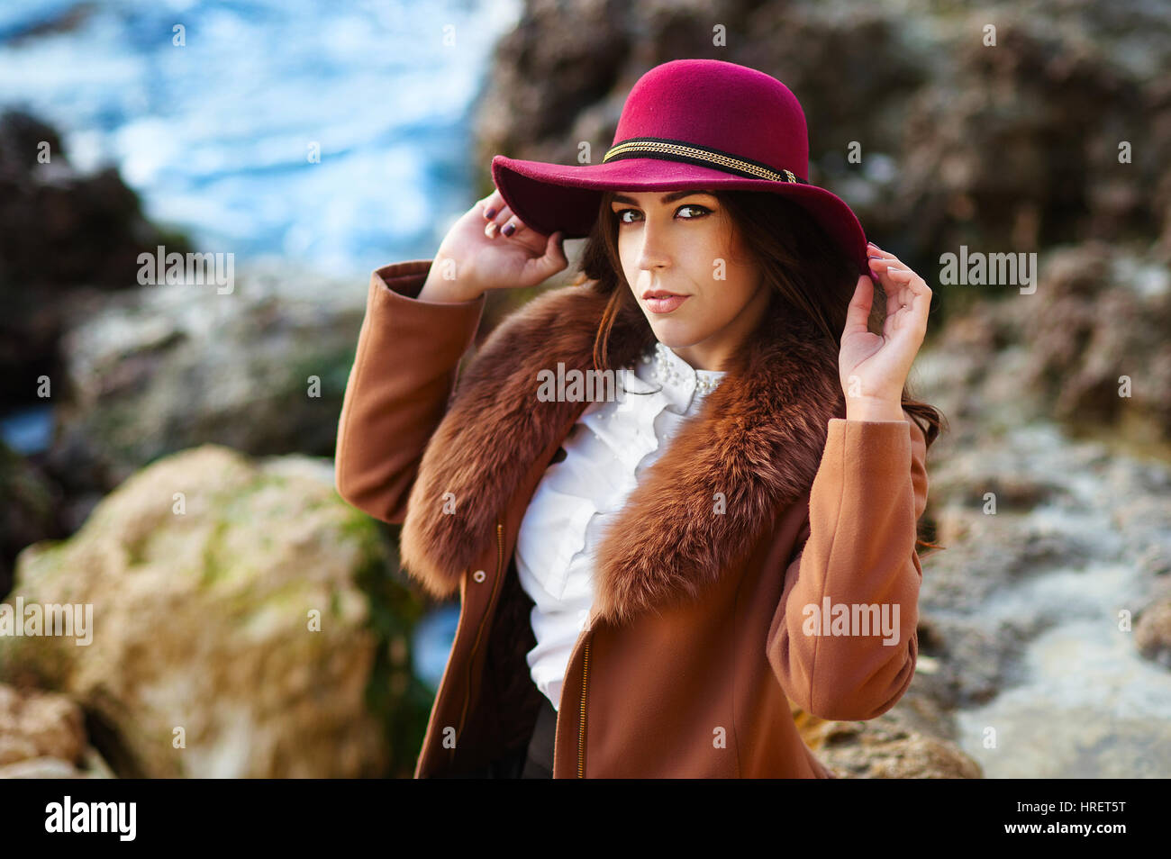 Cheerful lovely young woman in maroon felt hat and drape coat standing and laughing on pier in spring - Stock Image