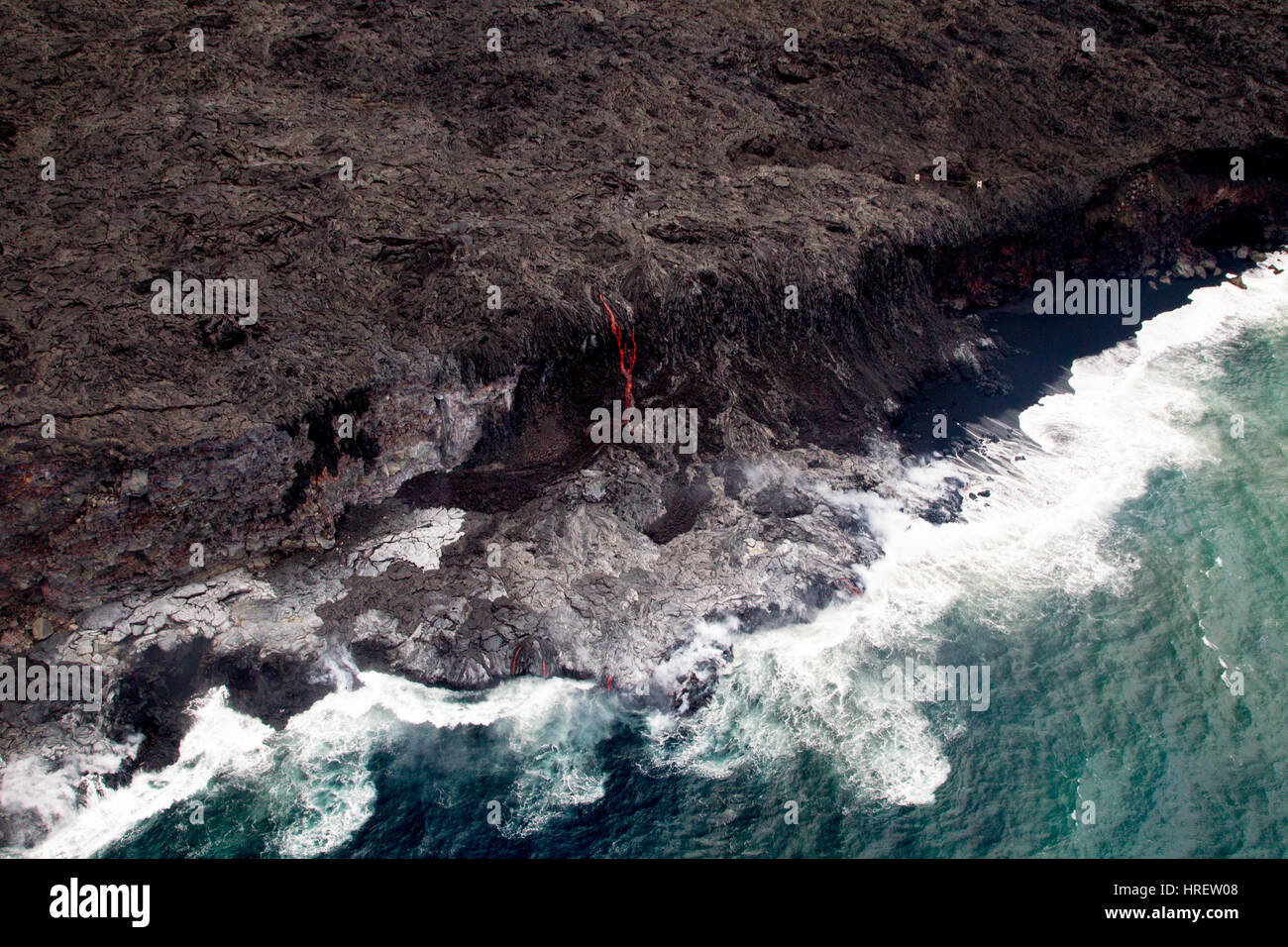 Aerial shot of red glowing lava flowing into the sea on the south coast of Big Island, Hawaii, USA. - Stock Image