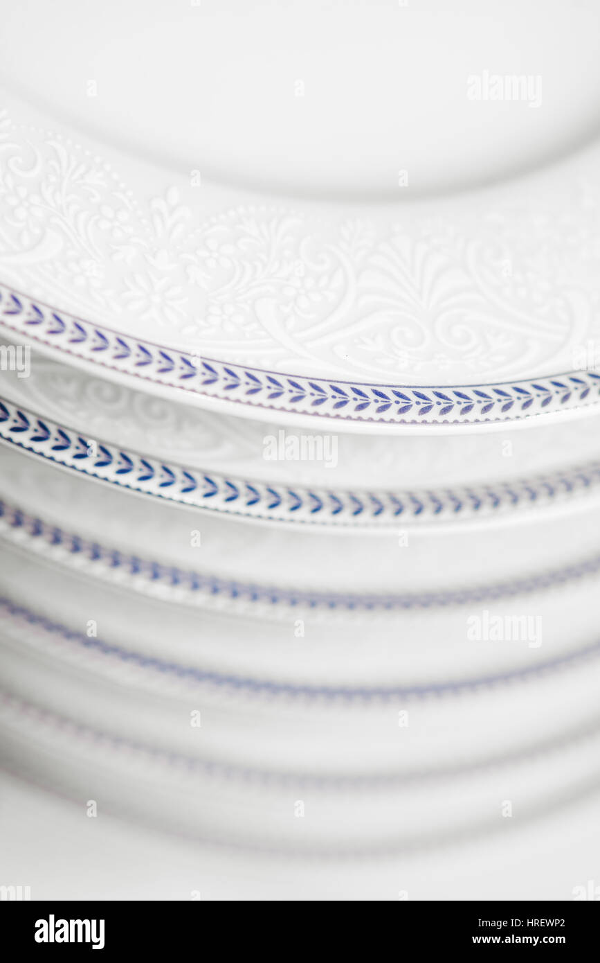 Clean white plates in cupboard - Stock Image