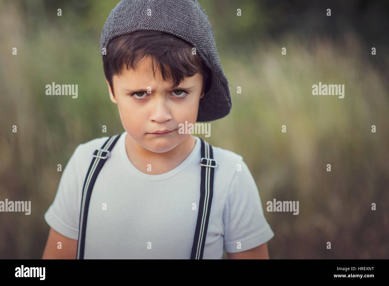 closeup of angry little boy with hat - Stock Image