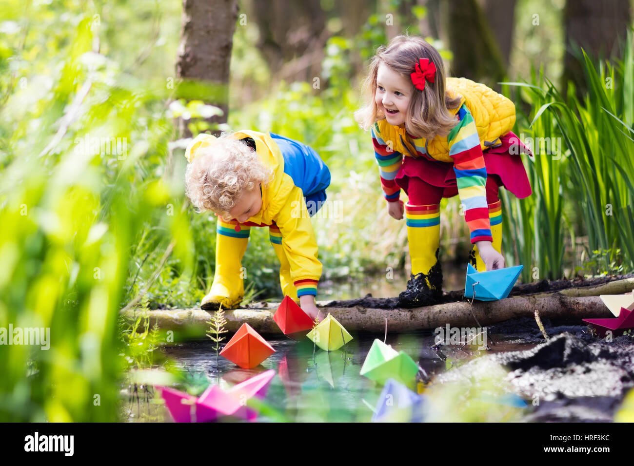 Children play with colorful paper boats in a small river on a sunny spring day. Kids playing exploring the nature. - Stock Image