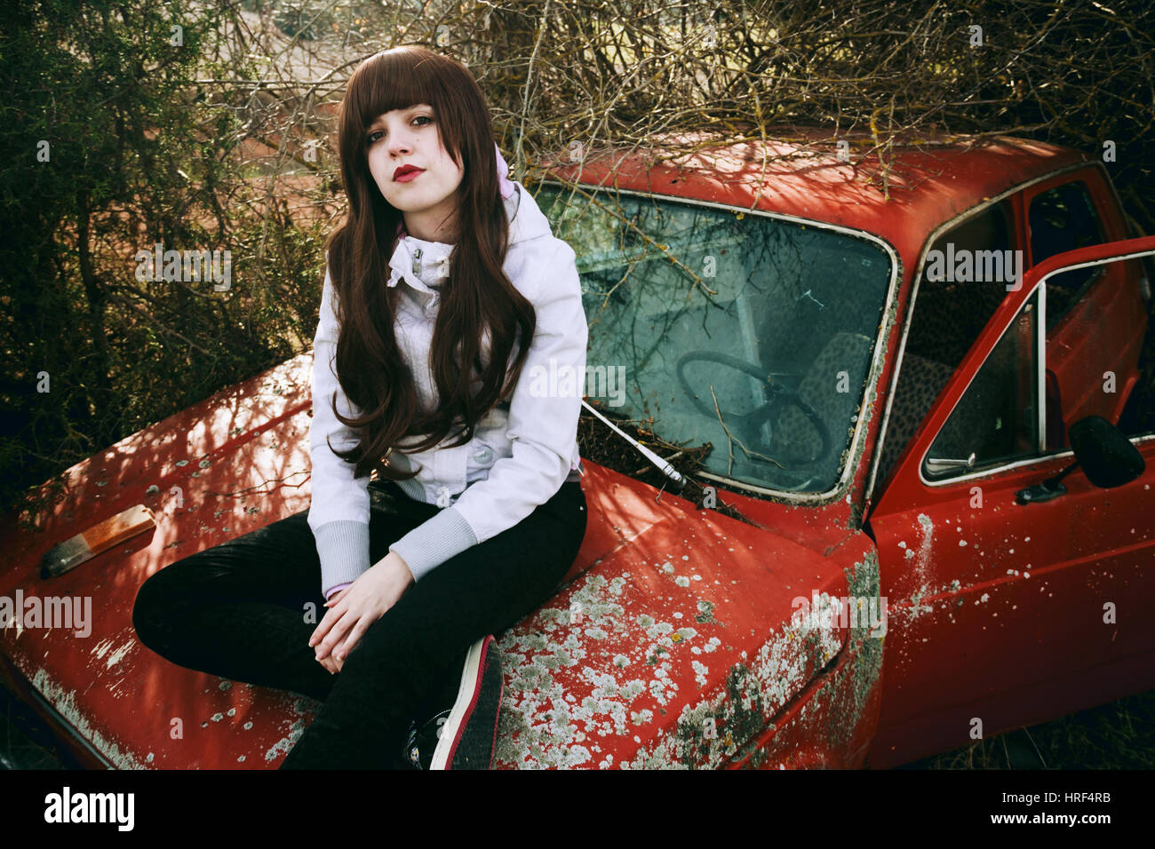 Young woman sitting in an abandoned retro car - Stock Image