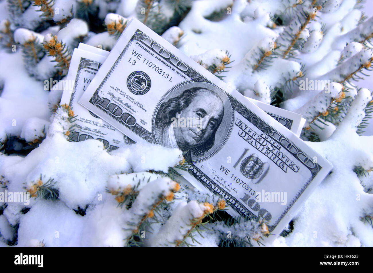 "Stack of 100 dollar bills lay half buried in the snow.  Image could represent ""cold cash"" and ""frozen assets."" Stock Photo"