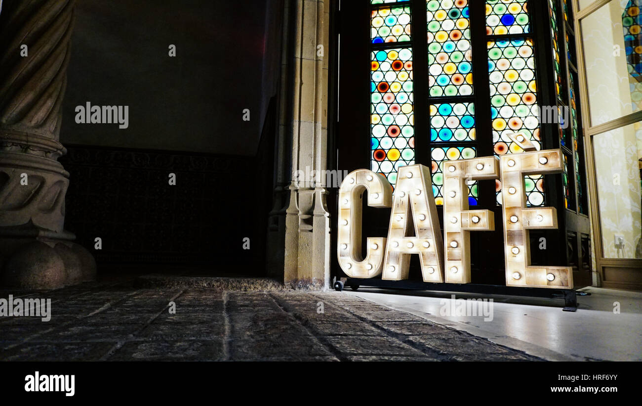 Low angle photo of a brightly lit cafe sign - Stock Image