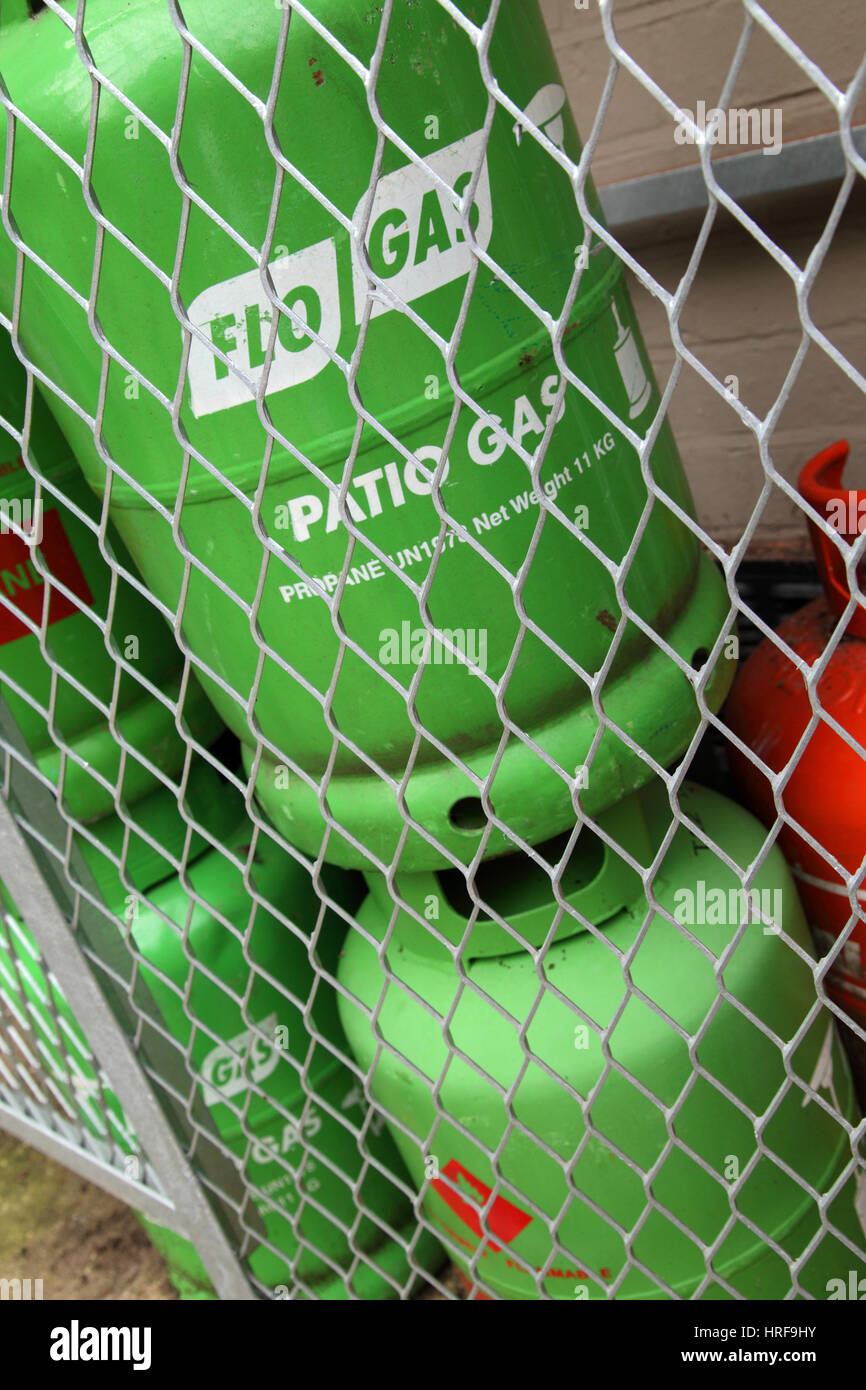 A stack of propane butane gas cylinders secured behind netting for safety. Flo gas, Calor gas. - Stock Image