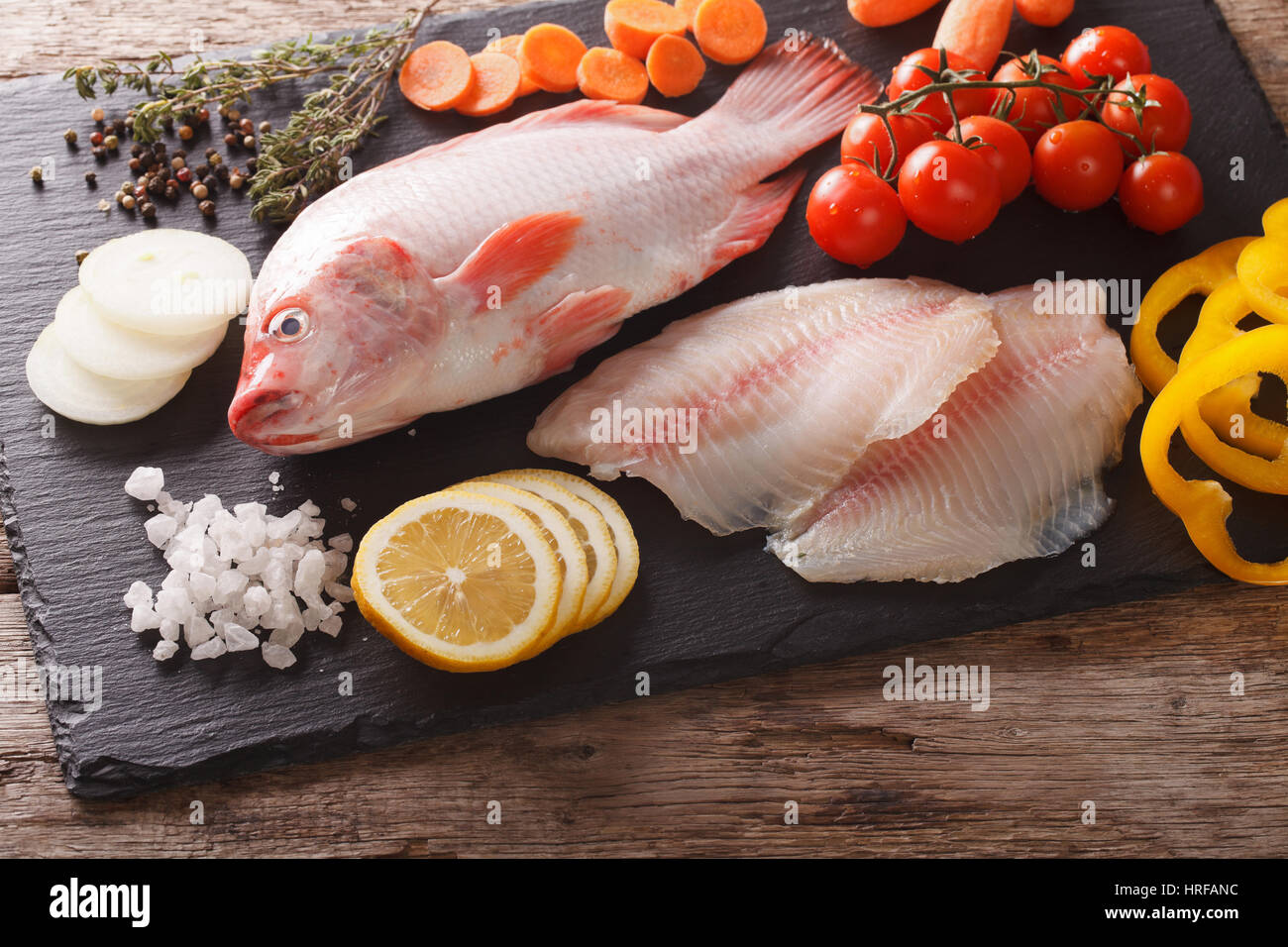 Raw whole tilapia, fillets and vegetable ingredients, spices close-up on the table. horizontal view from above - Stock Image