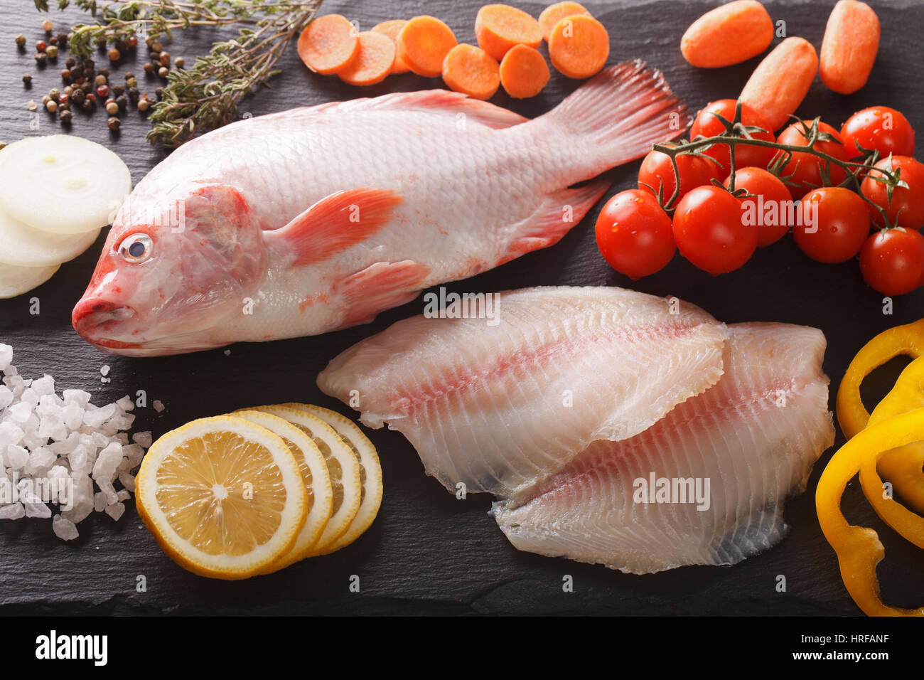 Raw tilapia and vegetable ingredients, spices close-up on the board. horizontal view from above Stock Photo