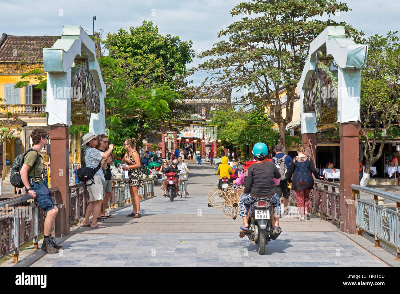 A typical street scene in Hoi An old town with tourists and local people walking, riding motor bikes across the - Stock Image