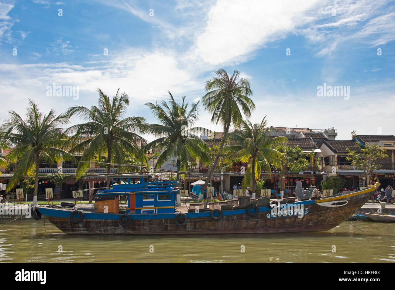 A view inl Hoi An old town with wooden tourist and fishing boats on the Thu Bon river next to the Cau An Hoi bridge - Stock Image