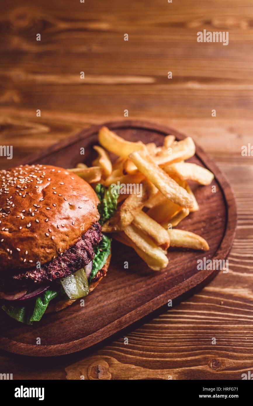 Top view on fresh burger and french fries on wooden table Stock Photo