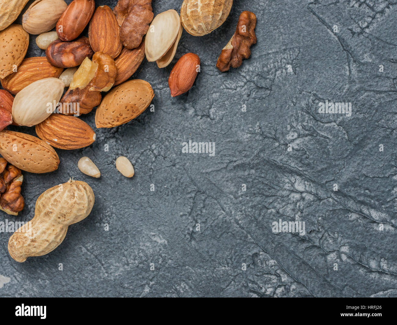 Background of mixed nuts - hazelnuts, walnuts, almonds - on dark concrete background with copy space. Top view or - Stock Image