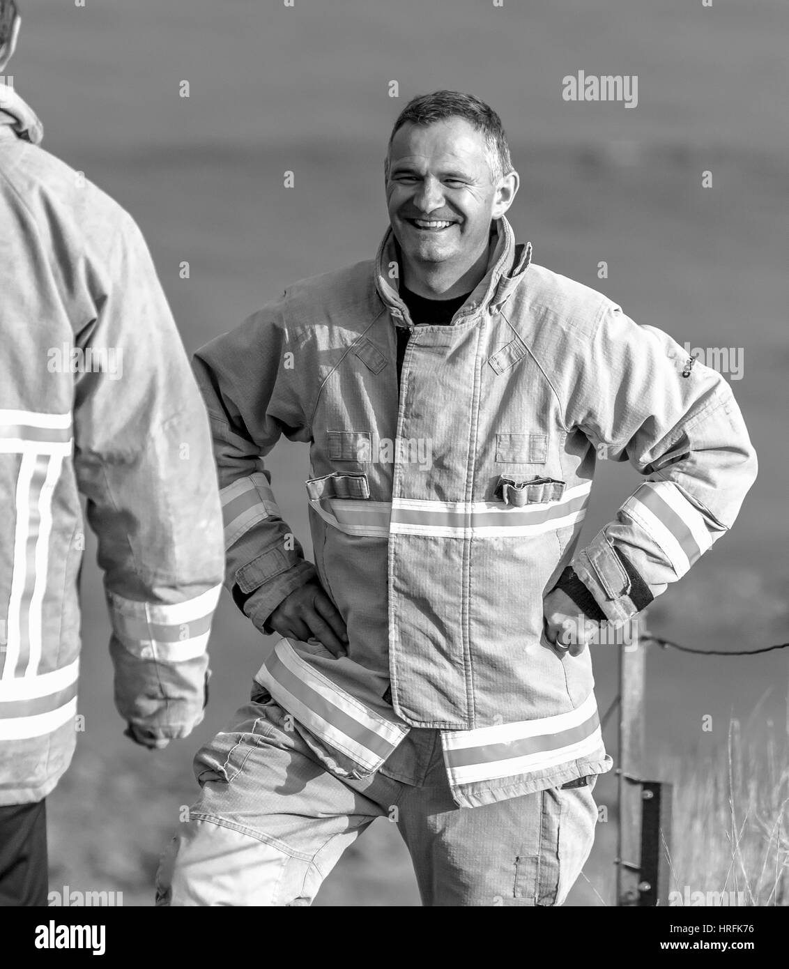 Fire officer smiling at conclusion of incident - Stock Image