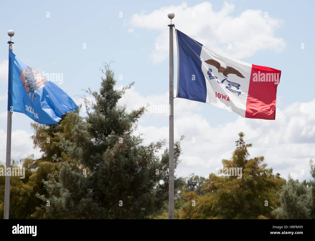 Iowa and Oklahoma state flags waving against blue sky - Stock Image
