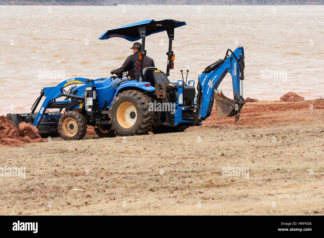 A workman moves dirt and rock with a Woods Groundbreaker BH70-X backhoe to shore up the bank of Arcadia lake. Oklahoma, - Stock Image