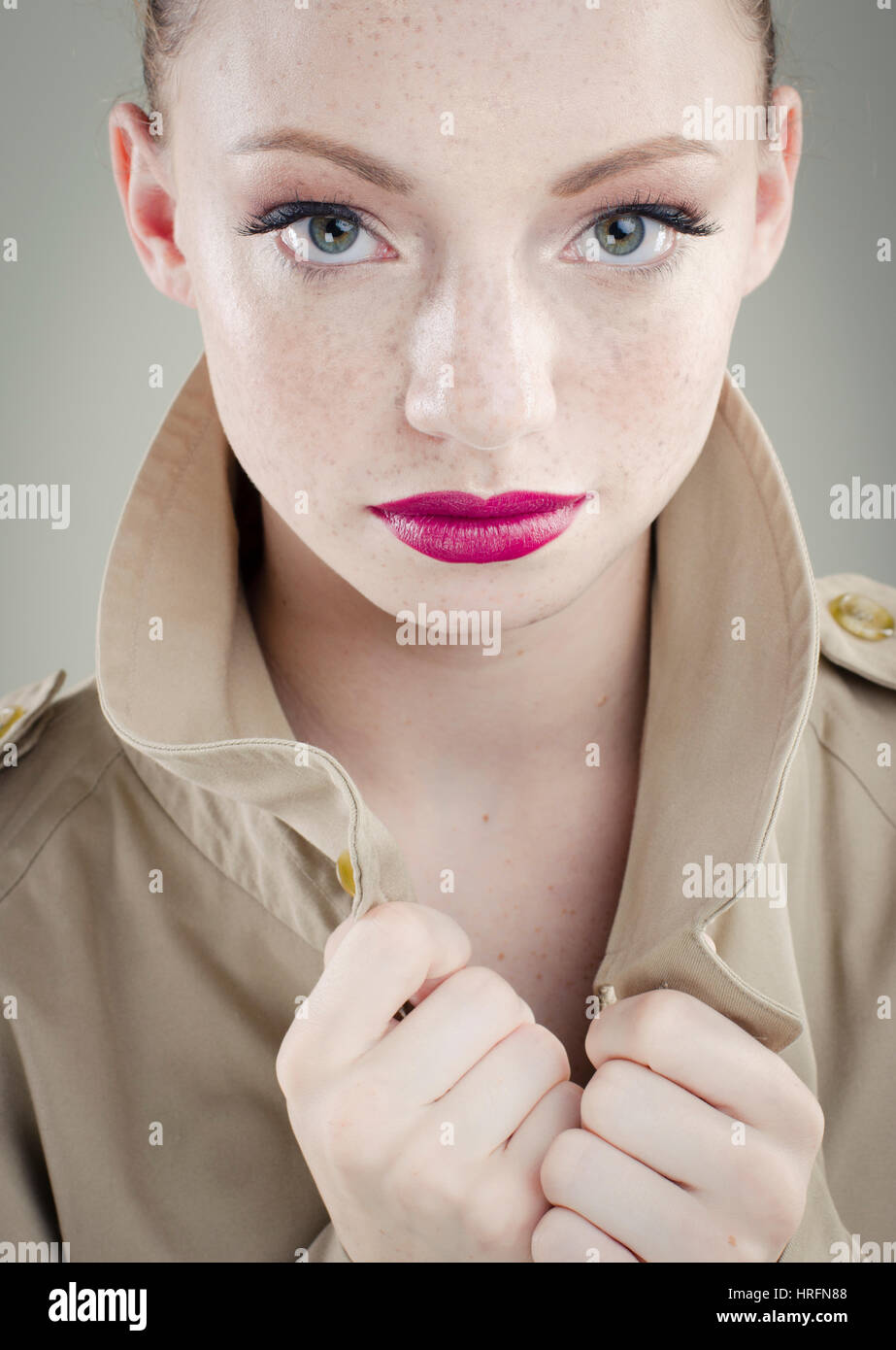 Young woman wearing trench coat - Stock Image