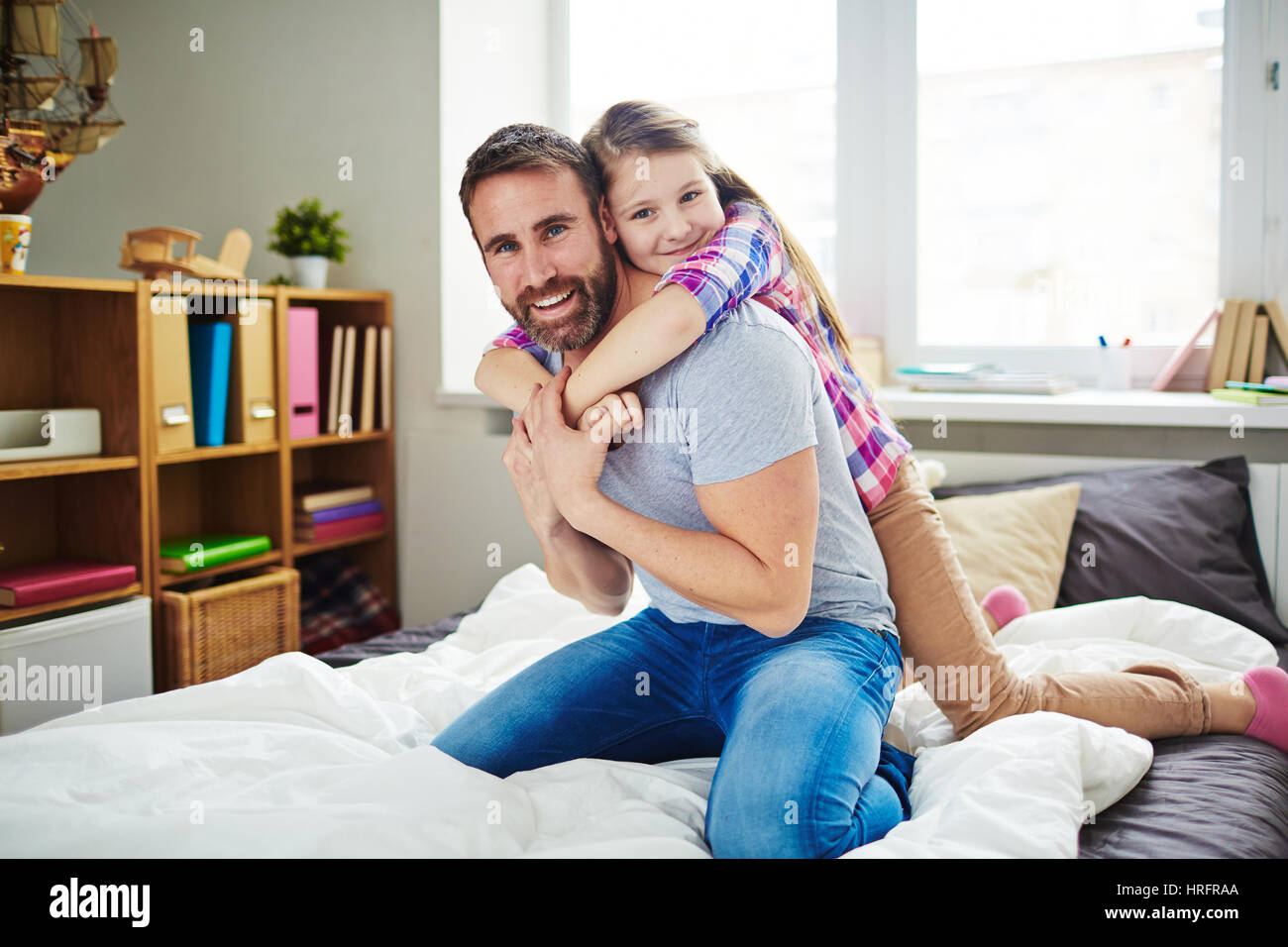 Cute little girl embracing her happy father tenderly while looking at camera with wide smile, full-length portrait - Stock Image