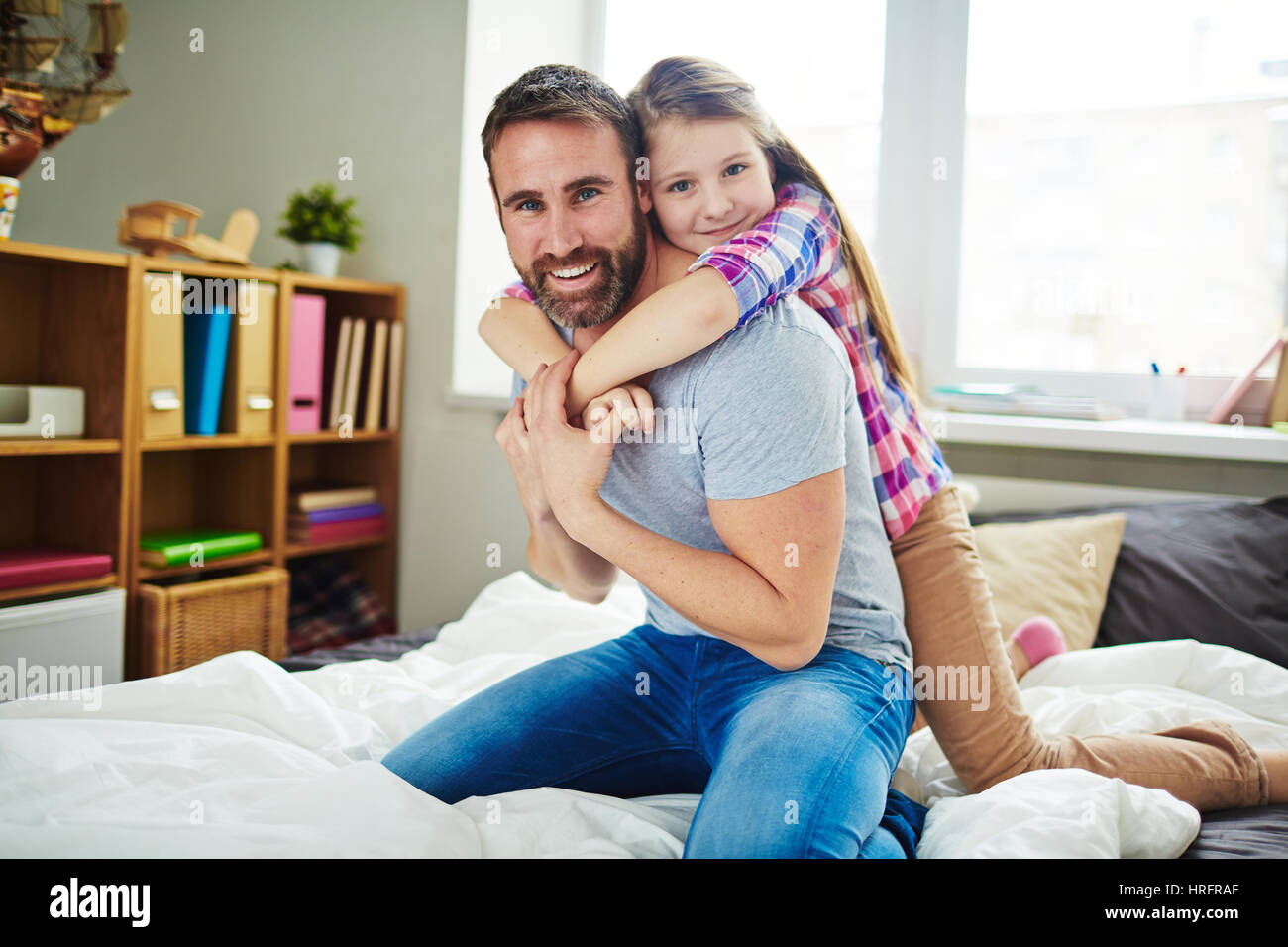 Teenage daughter and her dark-haired father standing on laps and looking at camera with smiles, girl hugging him - Stock Image