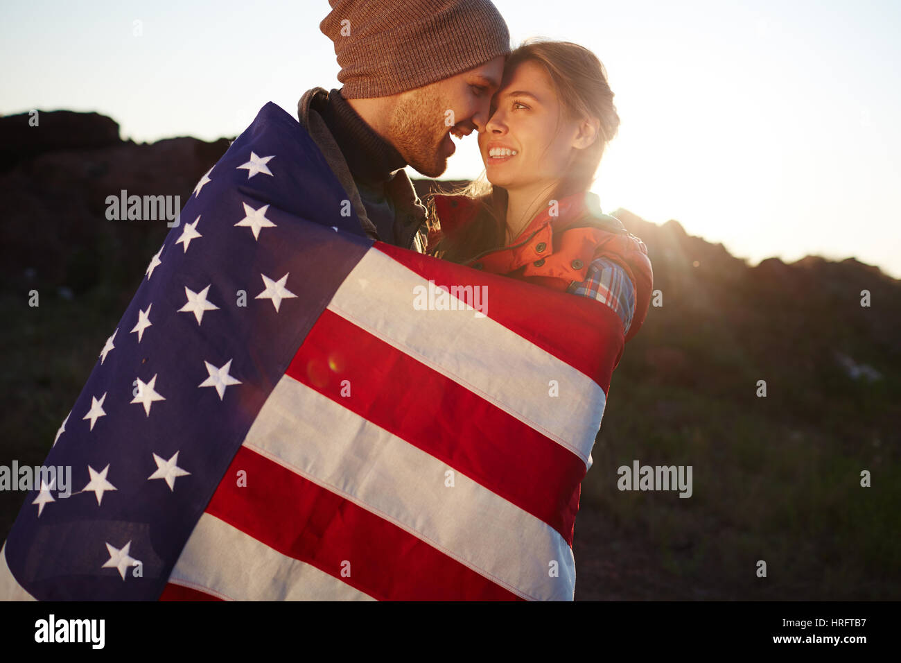 Portrait of young tourist couple standing close together in mountains, embracing tenderly wrapped in American flag - Stock Image